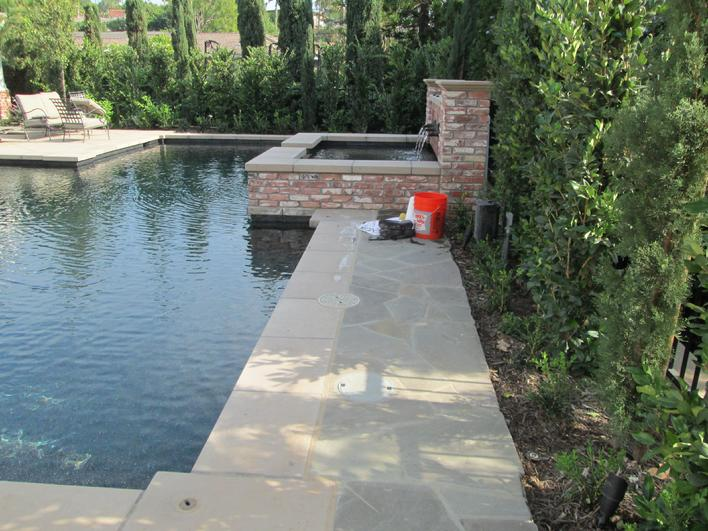 Picture of faded sealer on Flagstone Pavers by pool decking surround.