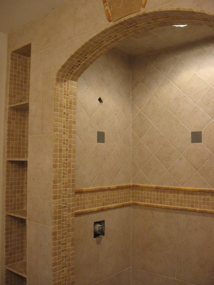 Travertine tile 1 inch mosaics and accent pieces for the borders and deco pieces installed with porcelian on a diagonal and with a subway pattern for shower and bathroom remodel with tiling as the focal point by a licensed tile contractors and installer working in San Diego